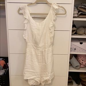 White, open back romper. Has light stripes